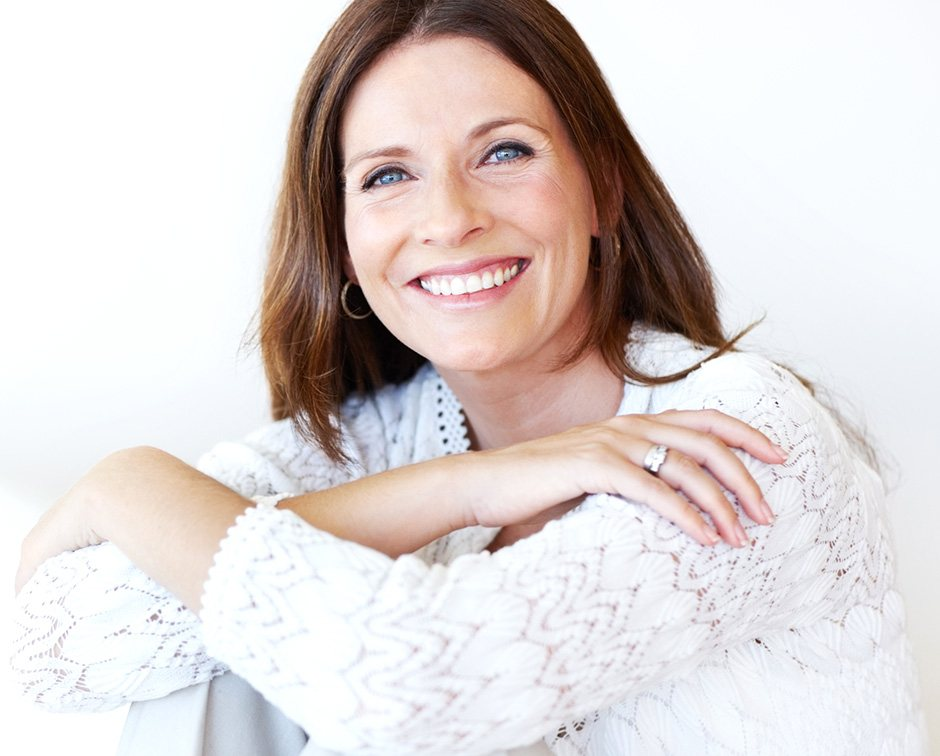 Smiling woman in white sweater with her hands over her knees