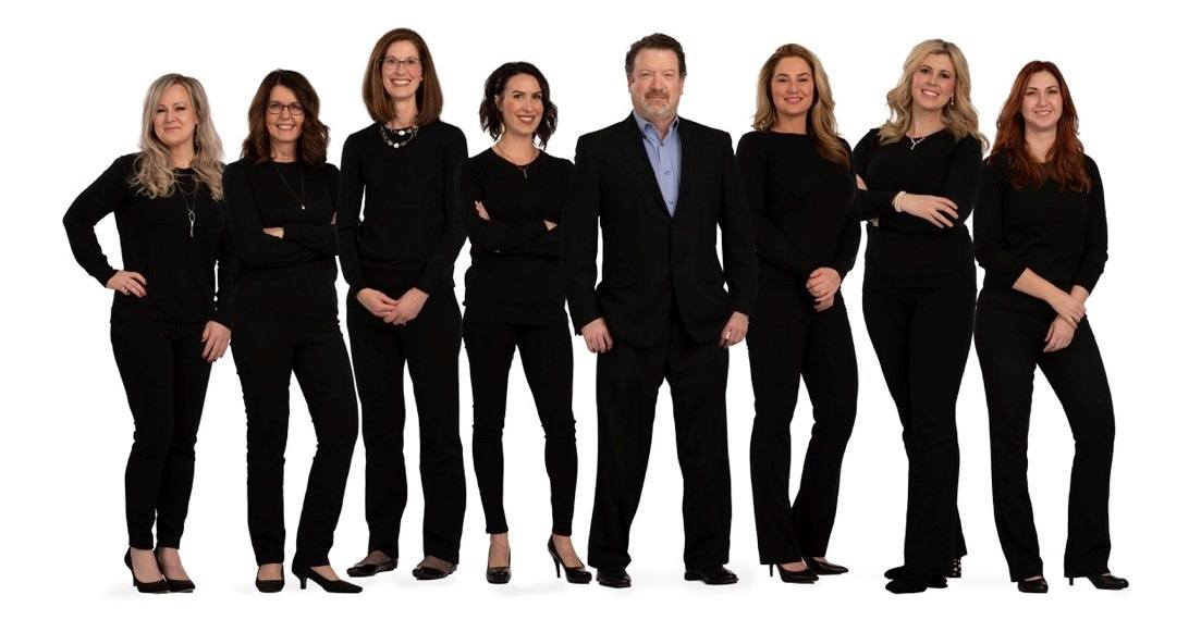 The Advanced Aesthetics team stands next to Dr. Kevin Johnson.